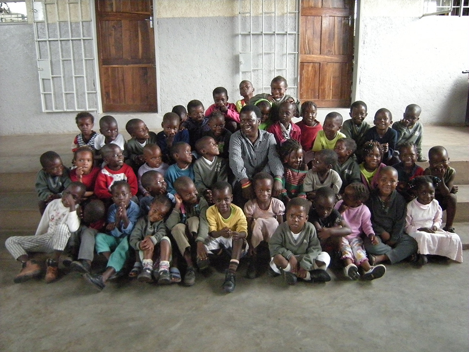 Angela Malik and the children of the Kondwa Centre for Orphans.  Since 2000, the Kondwa Centre has grown from a small pre-school to a full outreach and  educational centre that includes 4 classrooms, a library, kitchen, dining hall and playground - primarily through the support of Project ChildCare Foundation.